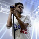 J. Cole holding microphone on stage